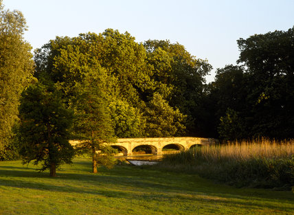 The bridge at the end of the serpentine lake, lit by the late evening sun