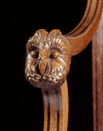 Details of owl mask carved on arm-rest of sabre-leg armchair in the Library of Melford Hall