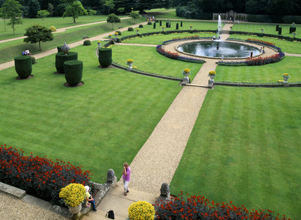 Close view of the Italian Garden at Belton House seen from the Orangery showing a pond surrounded by a circle of low stone walling enclosed in a square lawn with topiary, divided into quadrants