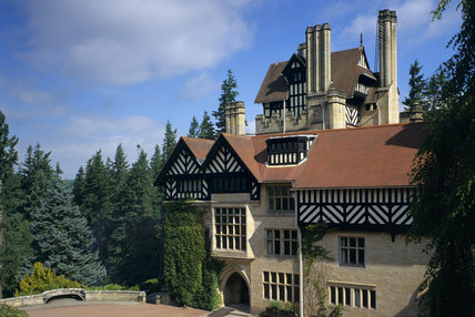 Close view of the entrance front at Cragside with the tower behind it, showing extensive half timbering under tiled gables and elsewhere,three chimney stacks and battlemented stone work