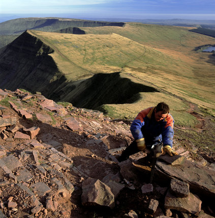 View of Robert Reith (National Trust warden on Brecon Beacons) shaping stones for path pitching. The steep path has slowly eroded due to large numbers of walkers.