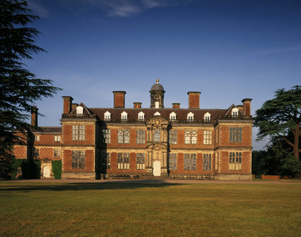 The north front of Sudbury Hall illuminated by the evening sun