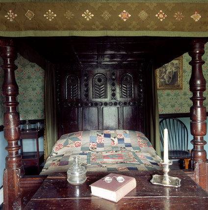Close view of a bedroom at Hill Top at Sawrey showing Beatrix Potter's tester bed and patchwork quilt,and a table and on it a book, a water flask and a pair of spectacles