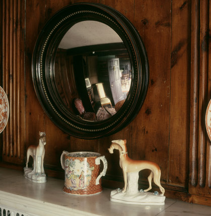 (FL) On the Parlour mantelpiece at Hill Top, beneath a Regency convex mirror are a Masonware double-handled pottery mug and a pair of C19 Staffordshire greyhounds with hares in their mouths