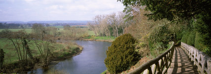 Wide view of River Wye from fenced walkway on top of steep embankment in the Weir Garden, Heds/Worcs