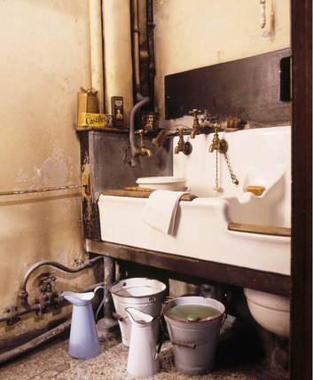 A Housemaid's closet fitted with a sink and slopsink at Dunham Massey, part of the modernisation of 1906, showing the original taps for hot, cold and soft water and enamel jugs and buckets