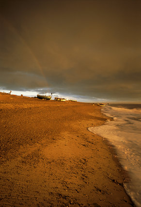 Waves rolling into shore at Dunwich beach with fishermen in the distance, and a rainbow falling onto their boats