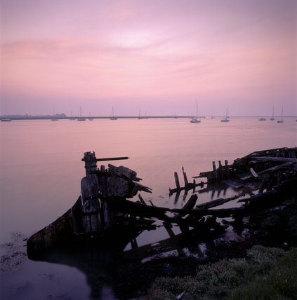 Wreck of a wooden boat at Orford Ness Quay at sunset
