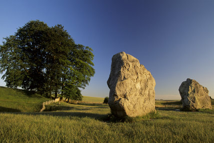 Two standing stones in the Circle and a tree standing out against the blue sky at Avebury