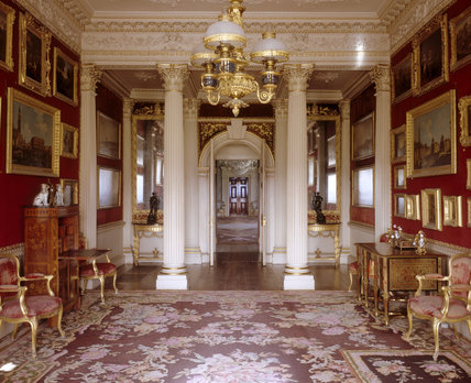 The red, white and gold Velvet Drawing Room viewed towards the arched doorway and columns