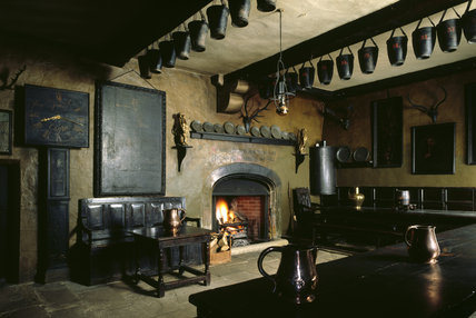 View of the Servants' Hall at Chirk Castle showing the oak table, oak settee and the John Jones clock of 1763