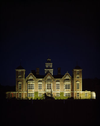 South front of Blickling Hall, floodlit at night, an imposing Jacobean house, with dark sky above and shadows in front
