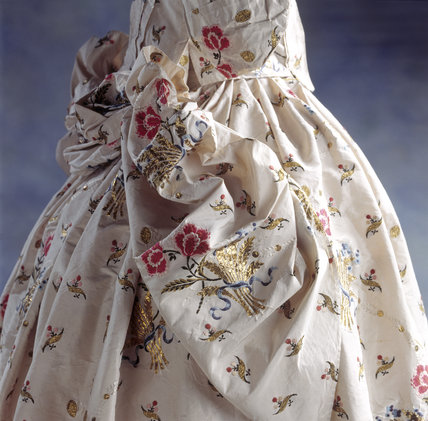 Close view of a Mantua Court Dress at Springhill showing embroidered flowers and leaves