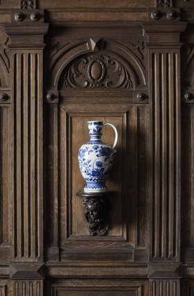 Blue and white ceramic jug on a wooden bracket in the wood panelled Garden Hall in the new house at Scotney Castle, Kent