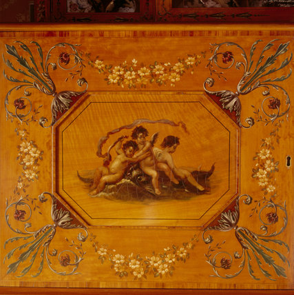 Detail of the left door, painted with putti, of the satinwood cabinet in the Morning Room at Cragside