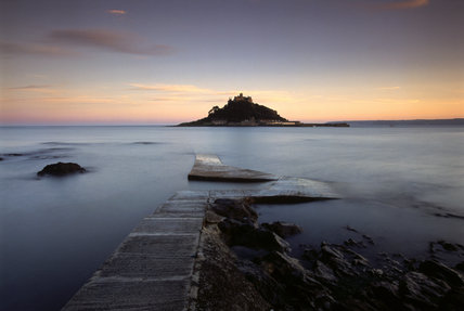 View of pink dawn rising behind St. Michael's Mount, with, in front, a calm sea and the causeway beginning to appear as the tide recedes.