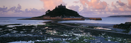 Fading light over St. Michael's Mount is relieved by a few pink- tinged clouds and silhouettes the island with its 12th century castle, church & exotic garden, harbour & cottages.
