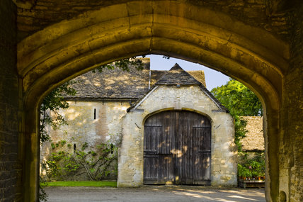 View through a stone arch towards the outbuildings at the fifteenth-century Great Chalfield Manor, Wiltshire