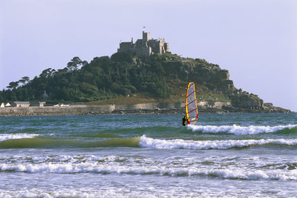 Medium view of the castle on St Michael's Mount silhouetted against blue sky, with waves breaking and an active wind-surfer in the foreground