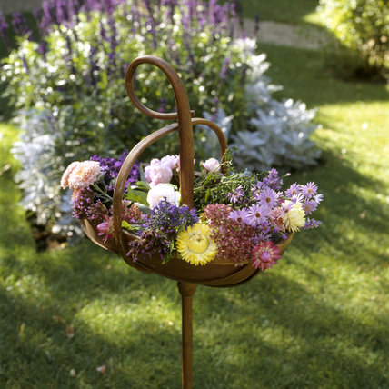 A trug-cum-walking stick in the garden at Peckover House filled with cut flowers including dahlias and asters