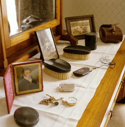 Close view of Dressing Table top displaying cigarette lighter, watch, spectacles, brushes, photographs, in Captain Lewes' bedroom at Llanerchaeron