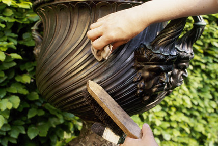 Cold waxing a bronze urn after applying microcrystalline wax