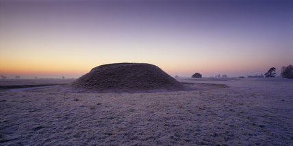 View looking towards a large burial mound at Sutton Hoo on a frosty dawn morning