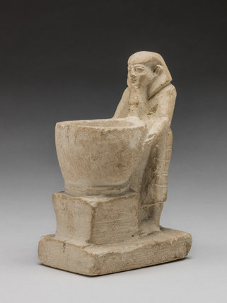 Egyptian limestone statue of a man with bowl