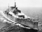 "HMS CUMBERLAND during ""pre-wetting"" trials in the Mediterranean, April 1954. Pre-wetting was a method of removing radioactive 'fall-out' from the ship's surfaces."