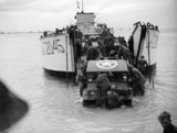 German POWs help unload a jeep from a tank landing craft near Ouistreham, Courseulles, 11 June 1944.