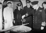 Admiral Sir Bruce Fraser pouring the rum into the Christmas pudding mix on board HMS DUKE OF YORK, November 1943.