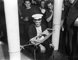 "Sailors surround the ship's cat ""Convoy"" asleep in a miniature hammock on board HMS HERMIONE, Gibraltar, 26 November 1941."