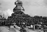The ship's company of HMS PRINCE OF WALES poses for a photograph with Winston Churchill and his staff at Scapa Flow after the Atlantic Meeting with President Roosevelt, 18 August 1941.
