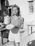 An emaciated internee, Miss Wendy Rossini, at Stanley Civil Internment Camp in Hong Kong, photographed after liberation in 1945 and showing the small quantity of rice and stew which served as rations for five people.