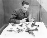 Flight Lieutenant J G Eadie, Medical Officer at RAF No. 11 Group headquarters at Uxbridge, photographed with part of his collection of model aircraft, 16 April 1943.