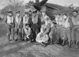 Squadron Leader Robert Stanford Tuck (centre) with pilots of No. 257 Squadron RAF under the nose of Tuck's Hawker Hurricane at Martlesham Heath. They are displaying souvenirs of their action against Italian aircraft on 11 November 1940.