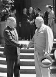 President Harry Truman and Winston Churchill shake hands on the steps of Truman's residence during the Potsdam conference, 16 July 1945.