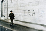 A soldier on patrol walks past IRA graffiti sprayed onto a wall in Newry in Northern Ireland.