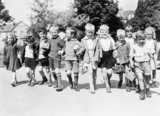 A group of smiling evacuees from Rotherhithe in Kent with gas mask boxes hold hands on a walk in Reading during 1940.