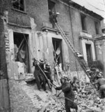 Members of a heavy rescue party evacuate civilians from a bomb damaged building during a large-scale Civil Defence training exercise in Fulham during 1942.