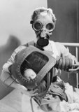 A nurse fitting a baby with its anti-gas respirator during the Second World War.
