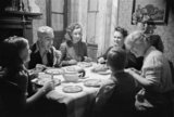Jane Meredith and Phyllis Morris of the Old Vic Travelling Theatre Company, enjoy a meal with Mr and Mrs Bailey, a miner and his wife, at their home in Trealaw, Wales during 1941. The children are Margaret and Douglas Ashington, evacuees from Birmingham.