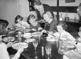 Mrs Carter enjoys Sunday lunch with her evacuated children Michael and Angela during a day trip to their foster home in Hayward's Heath in 1940.