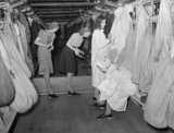 Female munitions workersstaff at an arms factory prepare for work in the factory changing area, 1940.
