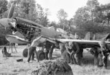 Men of an RAF Repair and Salvage Unit working on a damaged Supermarine Spitfire Mk IX of No 403 Squadron, Royal Canadian Air Force, at a forward airstrip in Normandy, 19 June 1944.