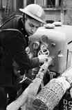 Auxiliary Fireman Norman Hepple switches on the water to the hose from a trailer pump, somewhere in London during 1940.
