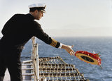 A naval officer on the Cunard liner COUNTESS laying a wreath into the water during a memorial service for those killed in the Falklands War, April 1983.