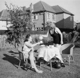 Peggy Franks and Pinkie Barnes enjoy tea in the garden as part of their 'holiday at home' in 1943.