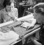 In the workrooms of the fashion designer Norman Hartnell in London, two women apply studs by hand to the belt and shoulder pieces of an afternoon frock, 1944.