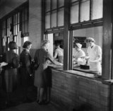 Members of the Women's Auxiliary Air Force catering section serve meals to WAAFs at the Royal Air Force depot in Uxbridge, 1944.